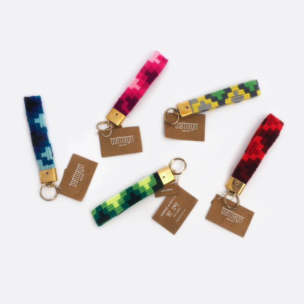 5 differently colored key chains: one has different shades of pink, one has different shades of blue, one has different shades of red, one has different shades of green and one is grey, yellow, and green