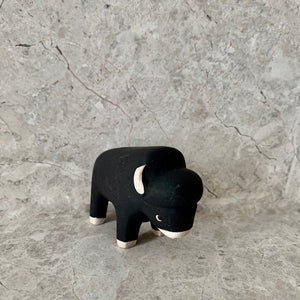 handmade and hand painted black wooden bison toy with white feet, ears and nose
