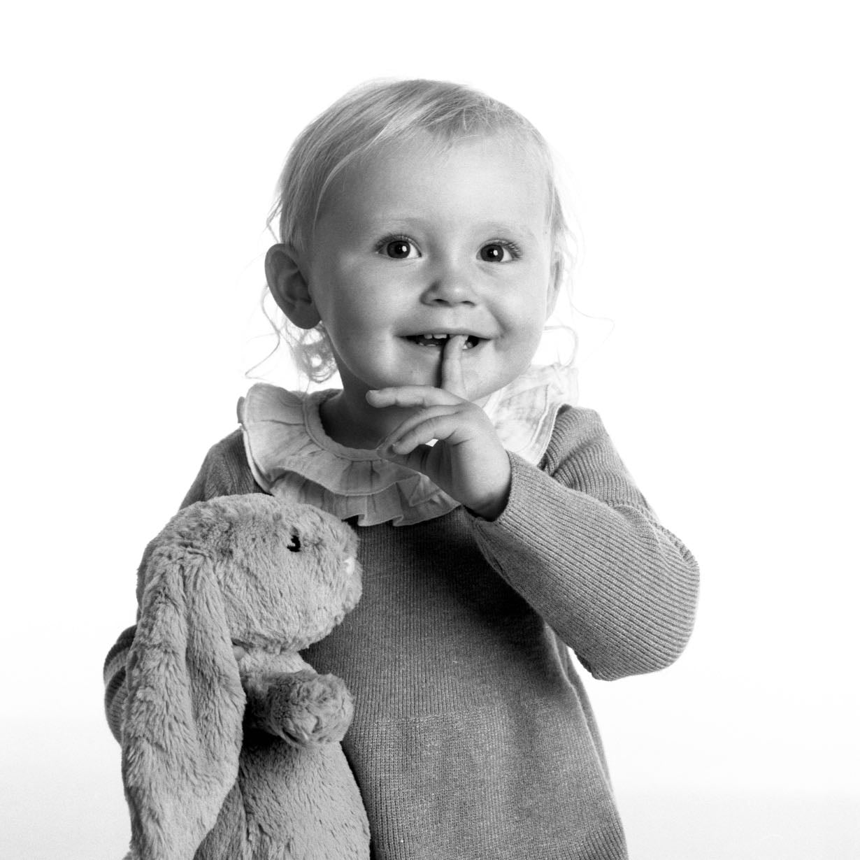 Portrait of a young child with toy in black & white by PHOTOGENIC Dalkey