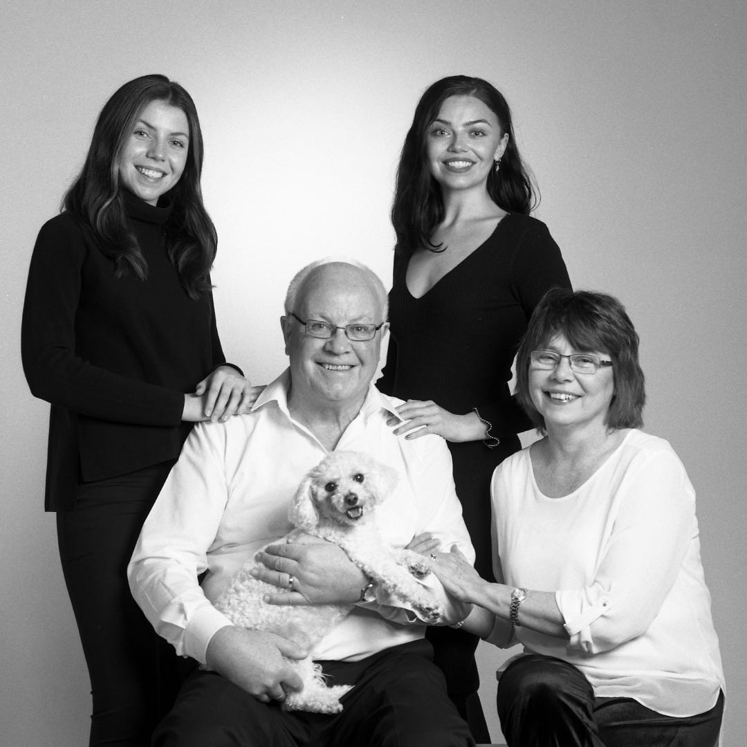 Family Portrait in black & white of a grown up family and their dog by PHOTOGENIC Dalkey