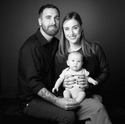 a black and white portrait of a young couple and their baby.