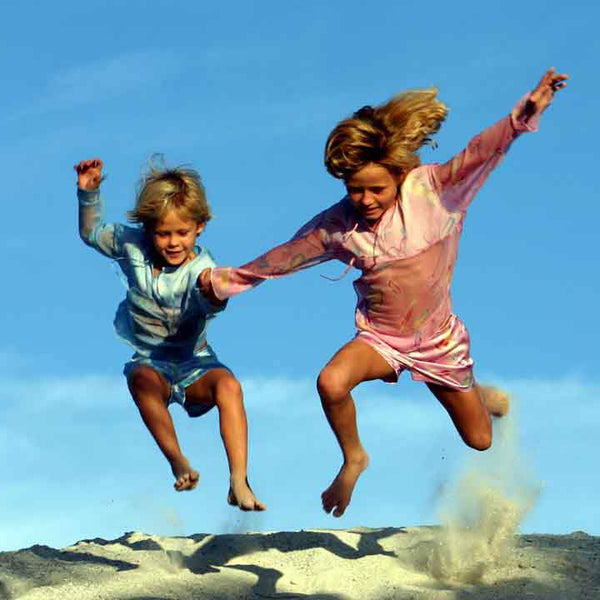 Sisters jumping in the sand, Mustique island, photographed by Lotty B