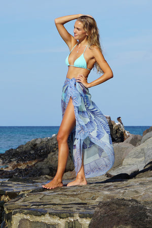 Large chiffon silk sarong scarf, Banana Tree print in blue designed by Lotty B Mustique worn with a turquoise bikini on Gelliceaux beach, Mustique