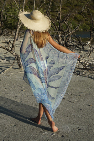Large chiffon silk sarong scarf, Banana Tree print in blue designed by Lotty B Mustique styled with straw hat and a chalk white bikini branches on the beach, Mustique