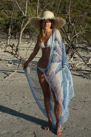 Large chiffon silk sarong scarf, Banana Tree print in blue designed by Lotty B Mustique styled with straw hat and a chalk white bikini from Pink House Mustique