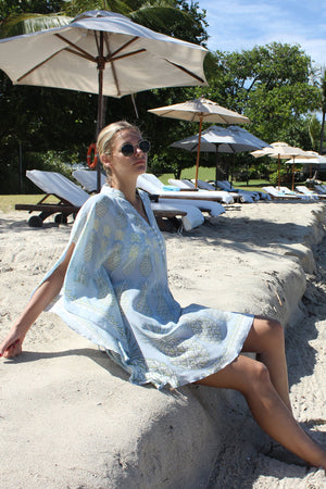 Lotty B Short Kaftan in Silk Crepe-de-Chine: PINEAPPLE - OLIVE sitting under an umbrella Mustique
