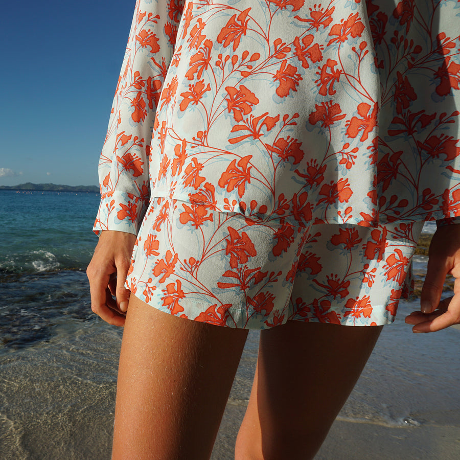 Bed to Beach shorts floral print orange on aqua blue designer Lotty B Mustique resort wear