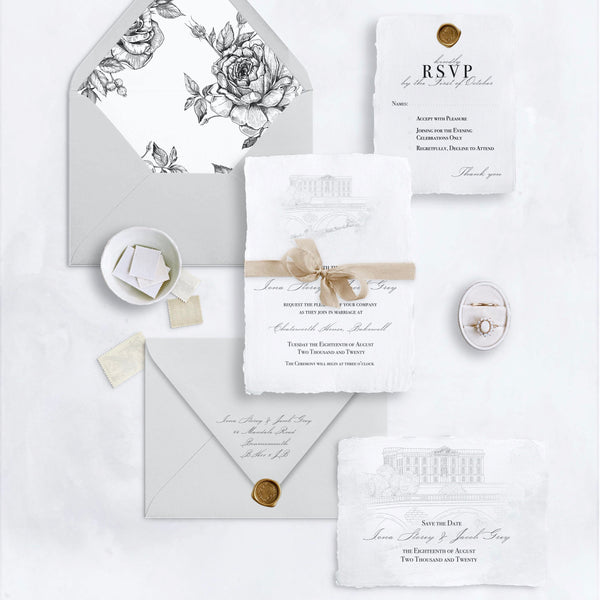 A flatly showing pale grey envelopes, and an invitation, save the date and RSVP card printed onto handmade paper.  The invitation and save the date cards have a hand-drawn illustration of a stately home.  Ribbons, vintage stamps, bronze wax seals and an engagement ring in a velvet box accent the paper.