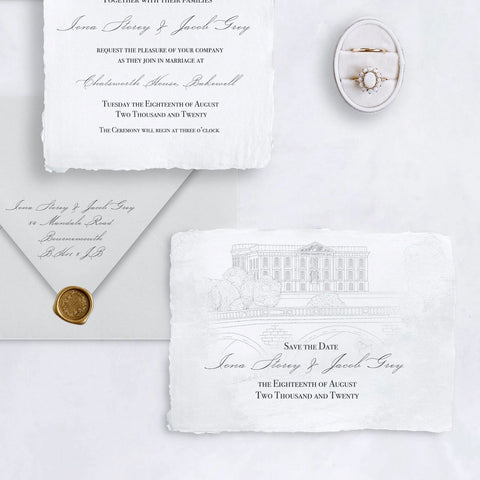 Save the Date wedding card, featuring a venue illustration on handmade paper.  To the top left, there is the bottom of the invitation with script writing, and a soft grey envelope, with return address printed on the back and fastened with a bronze wax seal. A ring box is seen in the top right.