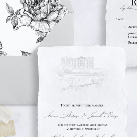 A wedding invitation on handmade paper, featuring a hand drawn venue illustration.  Behind it are the RSVP card on the same paper, and a soft grey envelope with a liner illustrated with roses