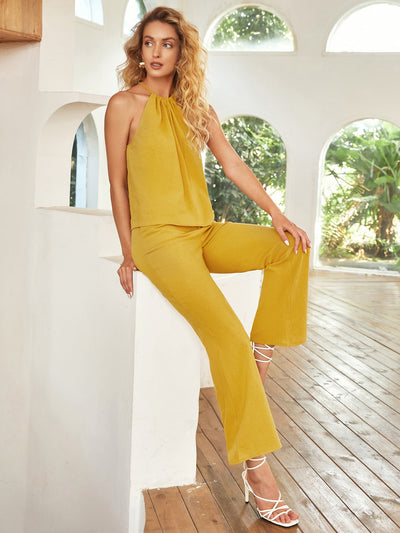 sleeveless plain halter neck mustard yellow top and double pocket flared pants set, female model view 1