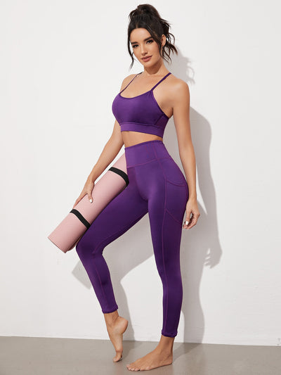 solid purple spaghetti strap cropped gym top and skinny fit leggings set, female model view 1
