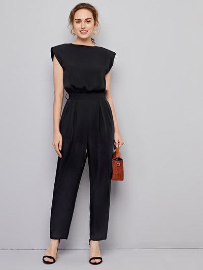sleeveless black round neck padded shoulder long pleated straight leg jumpsuit, female model view 1
