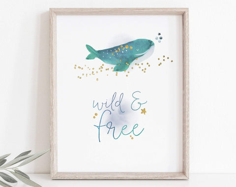 A print featuring a watercolour whale, with gold details. Underneath is the text 'Wild & Free'. The text is in blue and behind it there is a soft watercolour wash, also in blue. The background of the print is white.