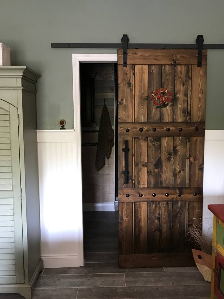 36x84 Wood Barn Door - Barn door is finished in dark walnut and wax sealed.  Embellished with iron clavos (nail heads) add character.  Red decor and front pull on door NOT included.