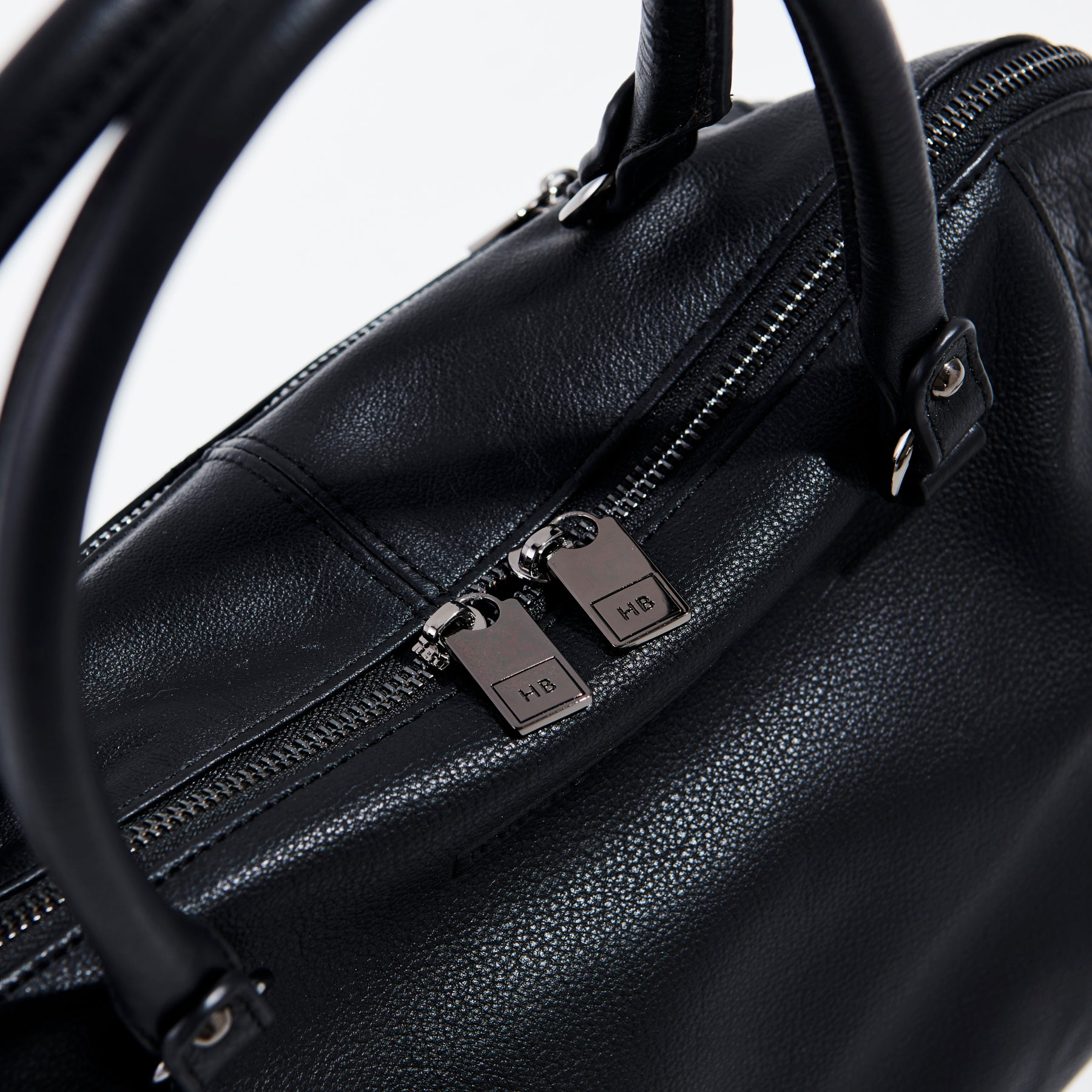 detailed view of double zip of black leather handbag