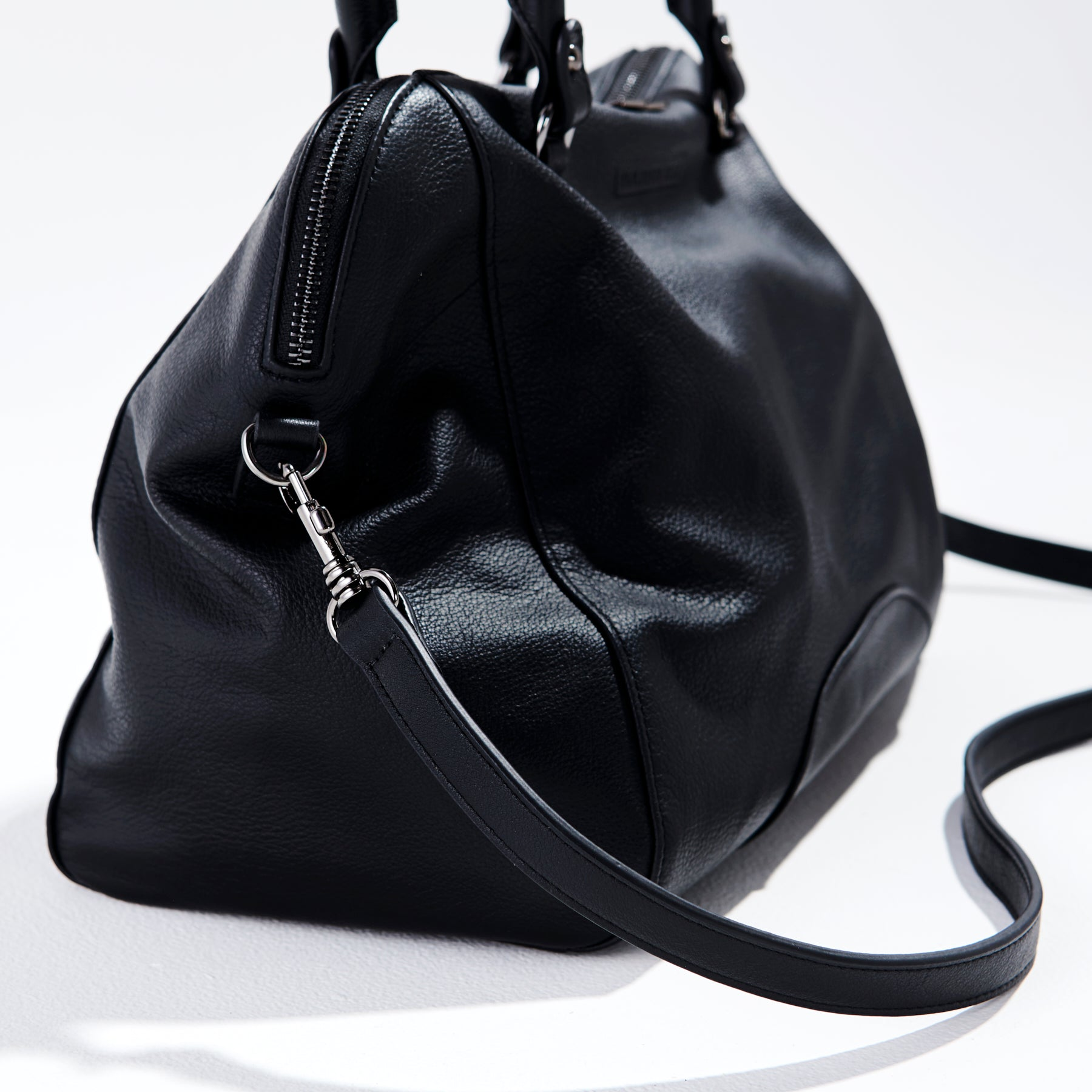 detail side view of black leather handbag