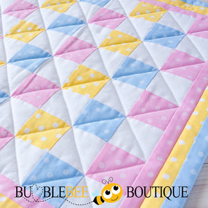 Close-up of Baby Dots pink, blue & yellow mini patchwork quilt front