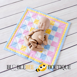 StandInBaby shows the size of the Baby Dots pink, blue & yellow mini patchwork quilt