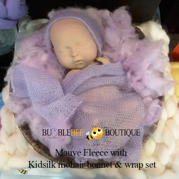 SIB resting on mauve fleece with kidsilk mohair bonnet & wrap set