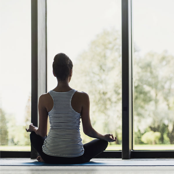 Meditation Boutique: A Beginners Guide to Meditating At Home. Image of girl meditating in front of floor to ceiling window.