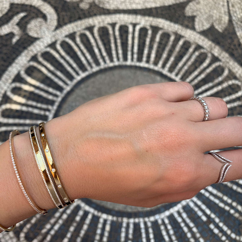 14K solid Gold (8.2g), 7 Diamonds (0.35 carats)  A gorgeous classic bangle bracelet with 7 perfect diamonds that would go perfectly alone or stacked for the perfect arm candy! The bangle has a safety clasp to keep it in place.   Available in Yellow, White and Rose Gold.