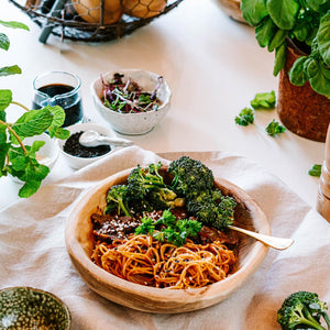 Beef Black Bean Noodle Stir fry on a table in a wooden dish