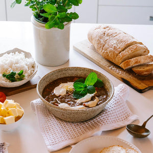 A beef hot pot on a table with sliced fresh bread and white rice