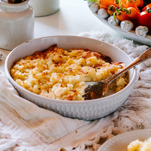 Close up of large bowl of potato bake with fresh vegetables in the background