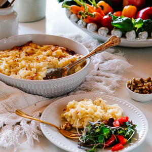 Large bowl of potato bake with single serving and salad on a dinner plate and fresh vegetables in the background
