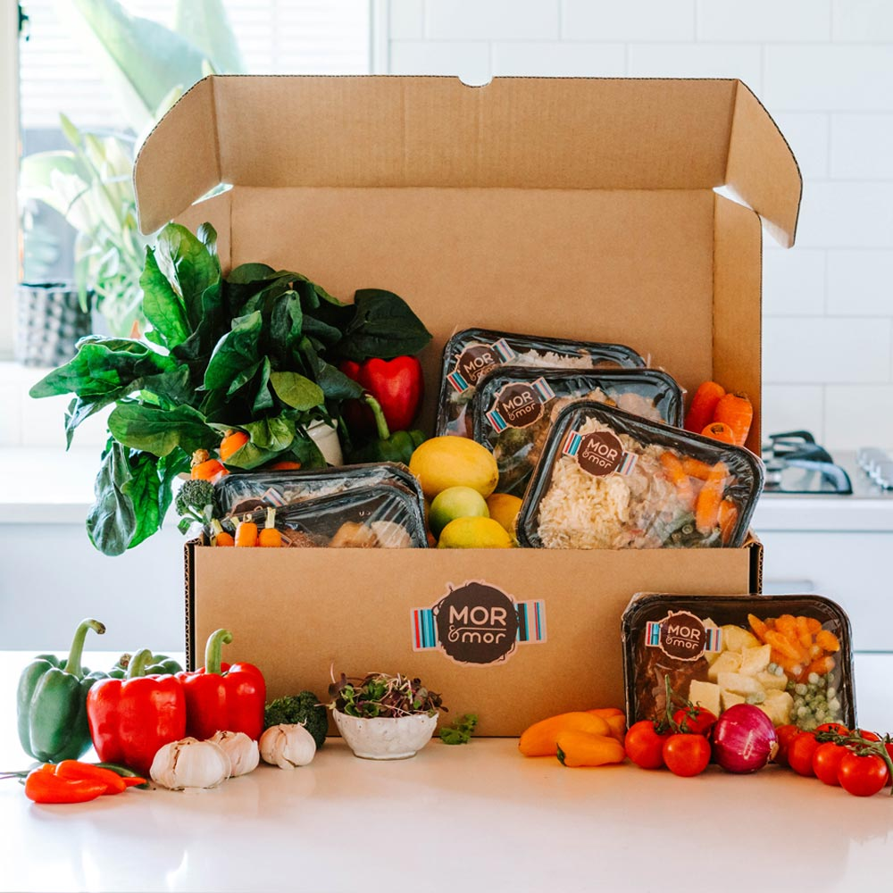 Shot of an open box with a selection of meals and vegetables spilling out