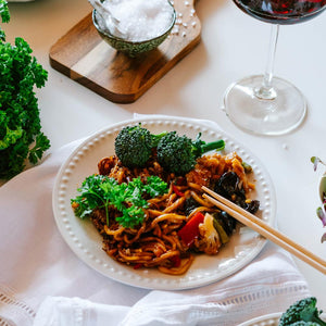 Shot of a dish of noodles on a napkin with chopsticks, salt and glass of red wine