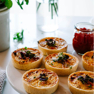 Different angle of six individual quiches on a platter with chutney in serving jar