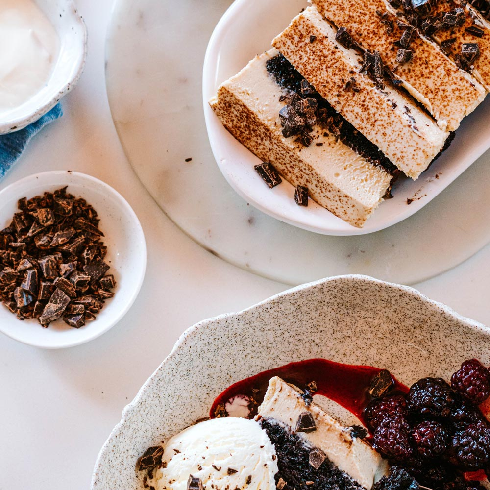 Sliced Tiramisu log alongside a serving suggestion of a serving of berries and ice cream
