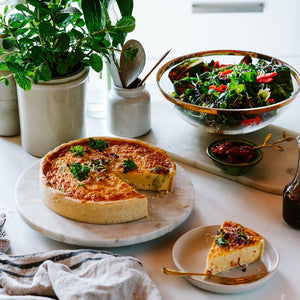 Family size quiche on a platter with a serving wedge and salad in the background