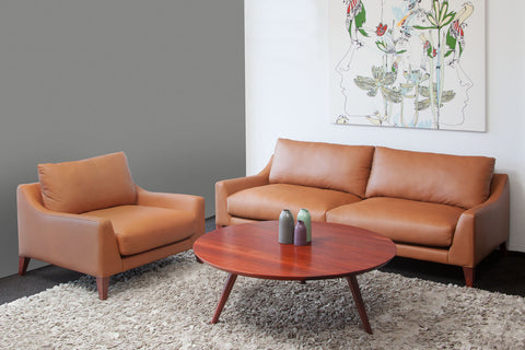 Round Retro Jarrah Coffee Table, tapered, angled legs with leather couch