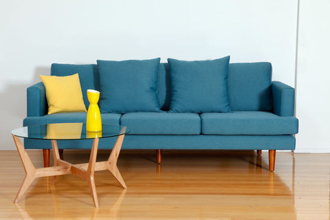 Spider Blackbutt Retro Round Coffee Table with Tempered Glass Top shown here with a retro blue couch
