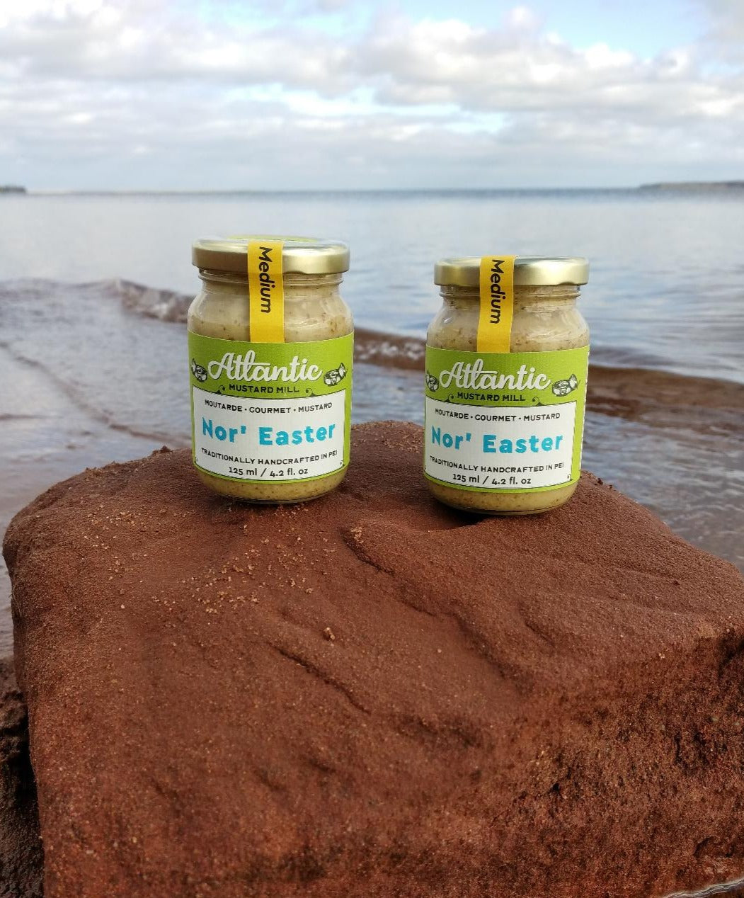 Two jars of mustard on a big stone on the beach with the sea in the background