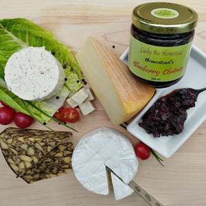 A board with a selection of cheese and a jar of blueberry chutney