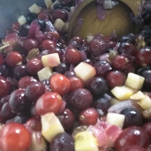 Pot full of cranberries and other ingredients stirred by a spoon