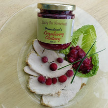 Load image into Gallery viewer, A glass of cranberry chutney on a plate with slices of turkey breast
