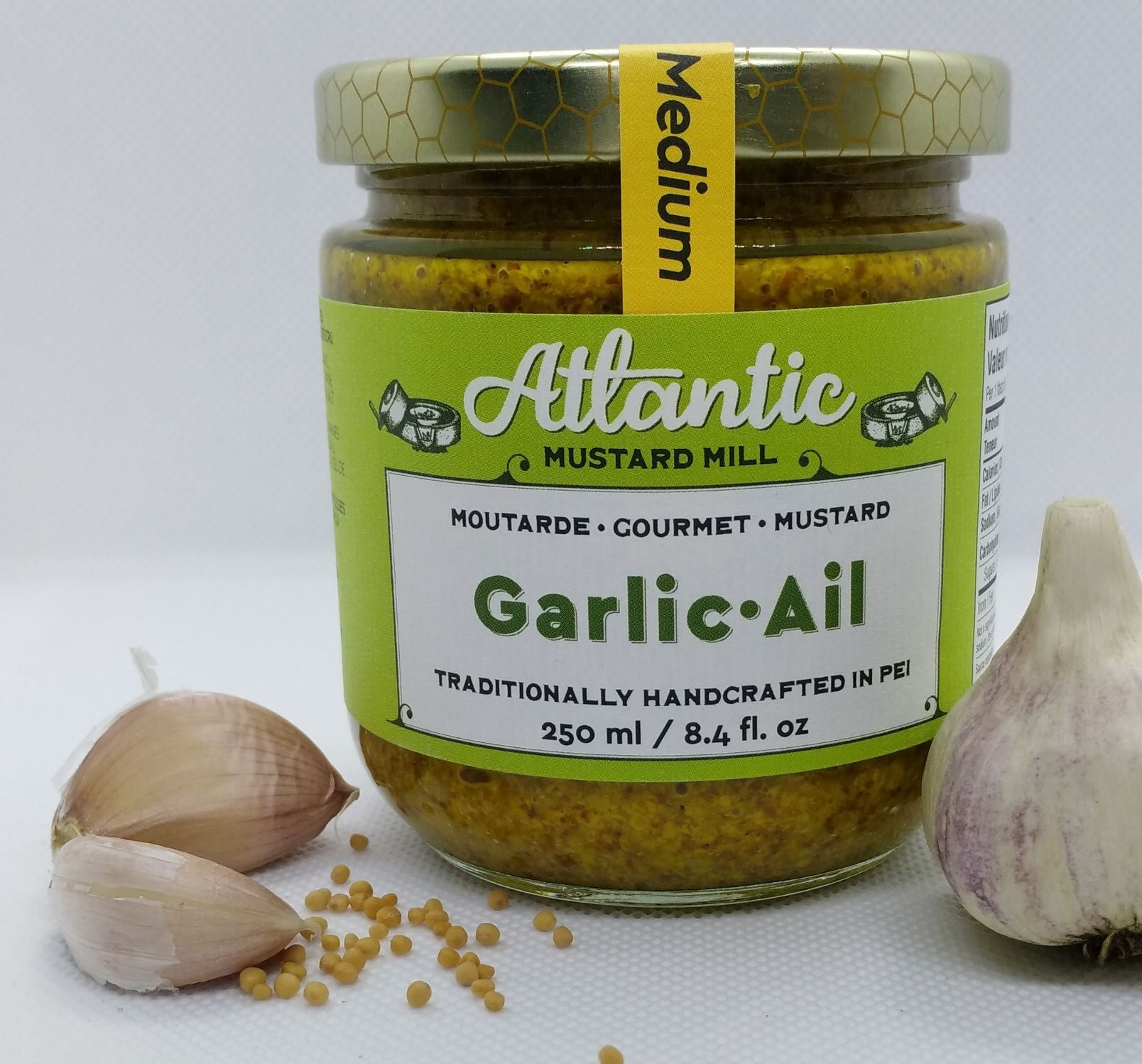 A bigger jar of mustard with a whole garlic and some cloves