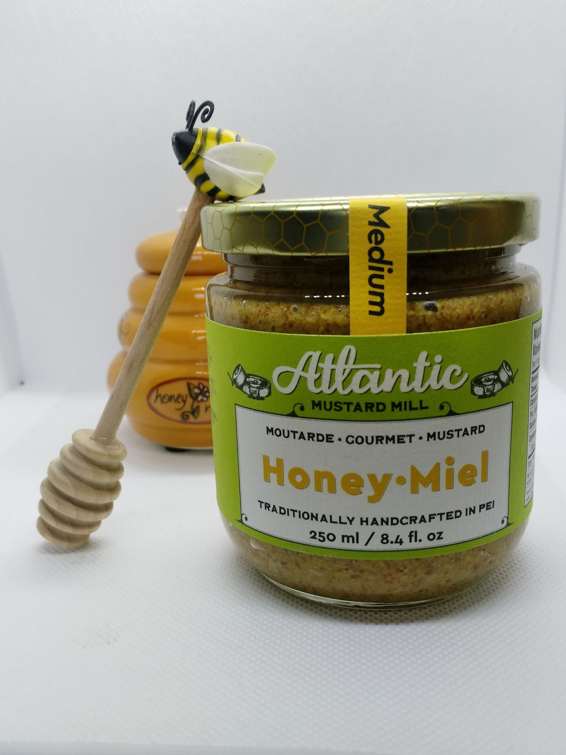 A bigger jar of mustard with a honey pot in the background and a honey spoon beside the jar