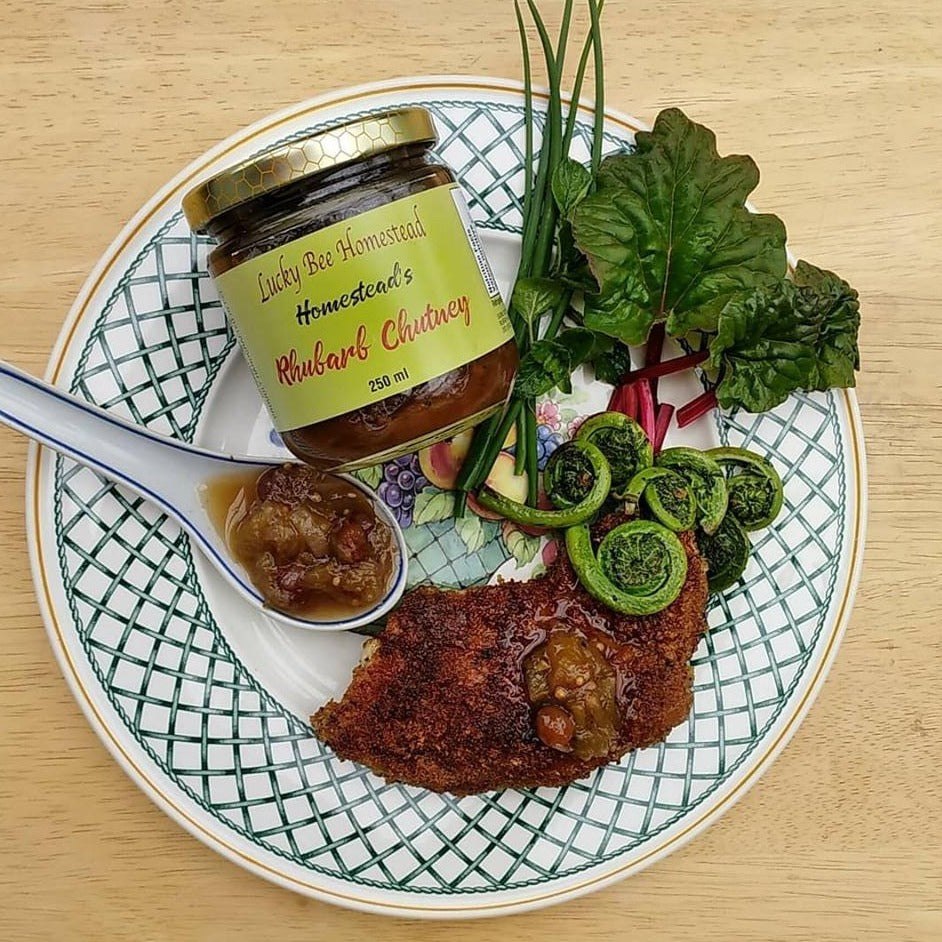 A plate with a schnitzel, a jar of chutney and fiddle heads