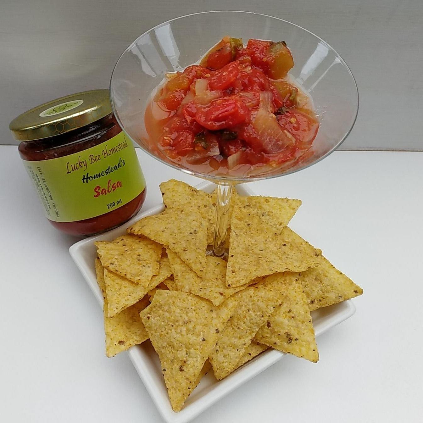 A cocktail glass with salsa, chips around it and a jar of salsa