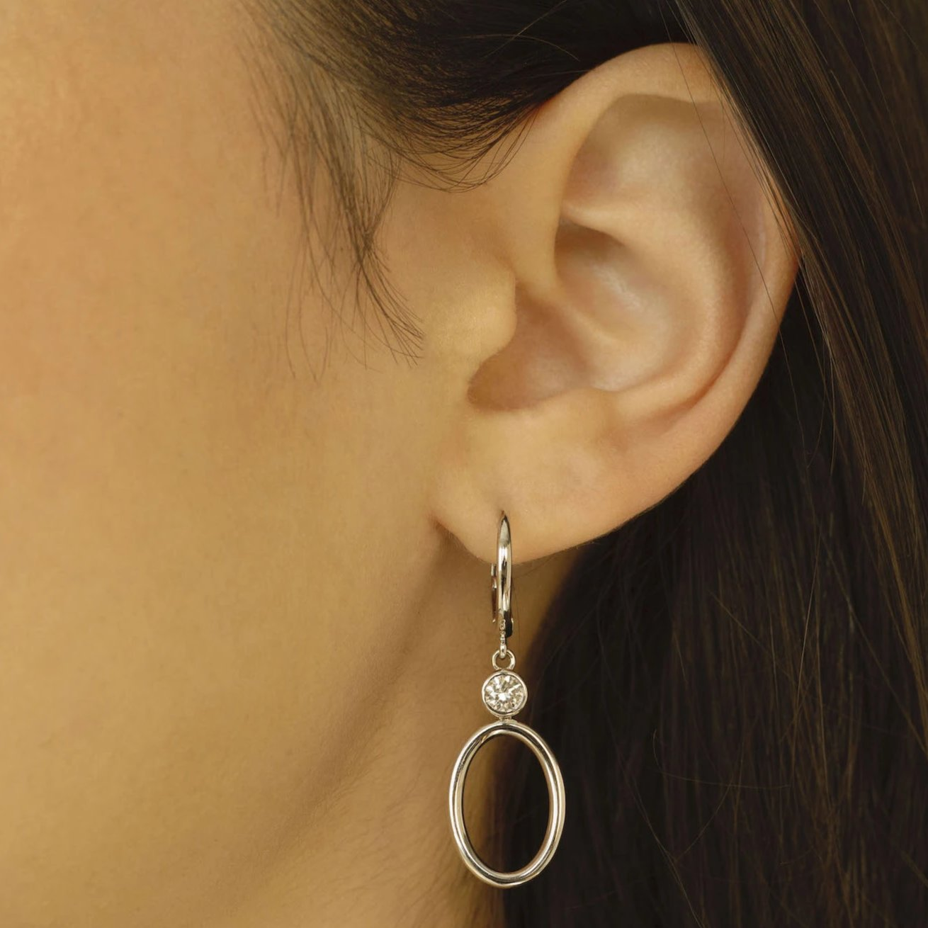 Woman wearing Henri Noël Jewelry white gold Drop Hoop earrings with bezel cut diamonds.