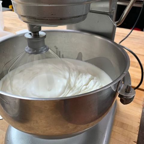 A standing mixer mixing whipped cream for gluten free eclairs