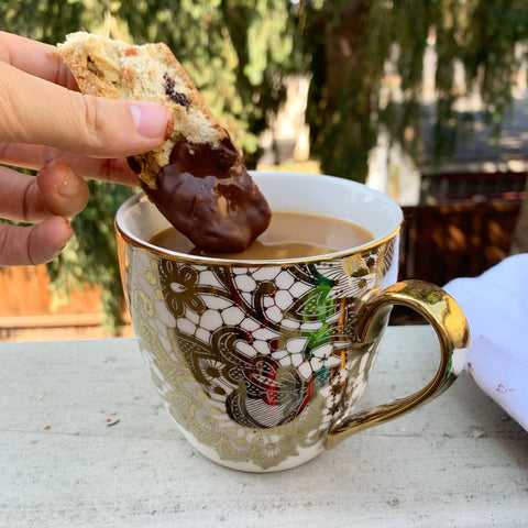 intricate tea cup with milky tea dipped gluten free biscotti