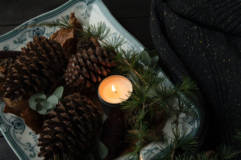 pine cones and lit candle holiday self care