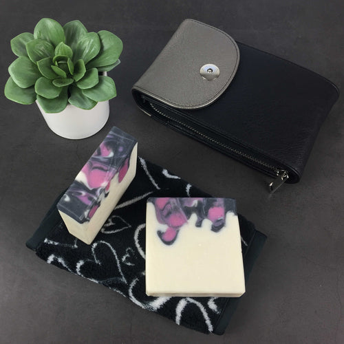 Black Raspberry Artisan Soap drop swirl design in raspberry, black, and white on slate background with a small black purse, houseplant, and beauty towel